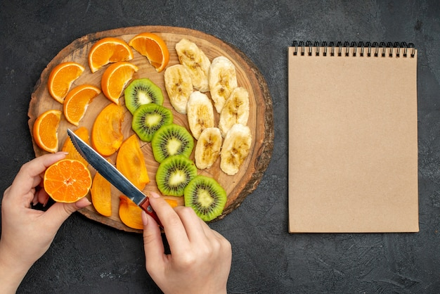 まな板と暗い背景のスパイラルノートに設定された天然有機新鮮な果物の上面図