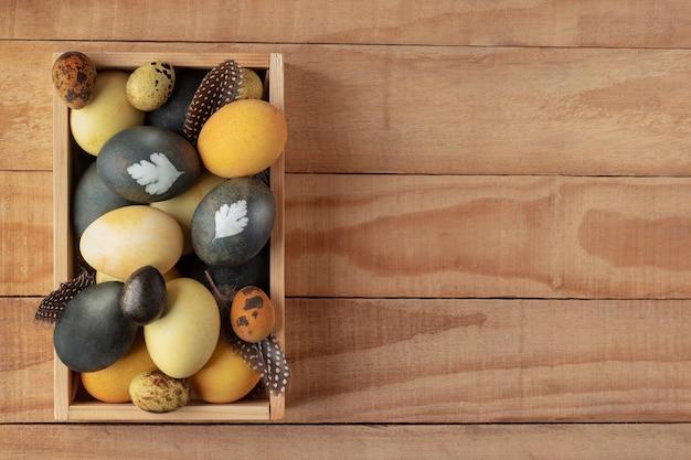 Вид сверху естественно окрашенных пасхальных яиц в коробке на деревенском деревянном фоне