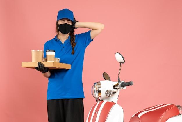 パステル ピーチ色の背景にコーヒーの小さなケーキを保持しているオートバイの隣に立っている医療マスク手袋を着た神経質な宅配便の女の子のトップ ビュー