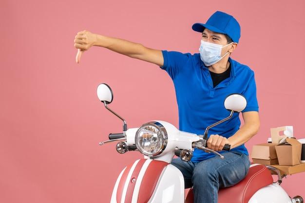 Вид сверху нервного доставщика в медицинской маске в шляпе, сидящего на скутере и делающего плохой жест на пастельном персиковом фоне