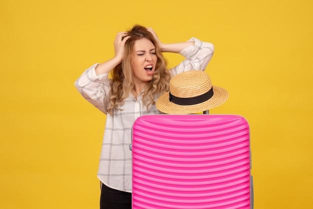 彼女のピンクのバッグの後ろに立っている神経質な感情的な若い女性の上面図