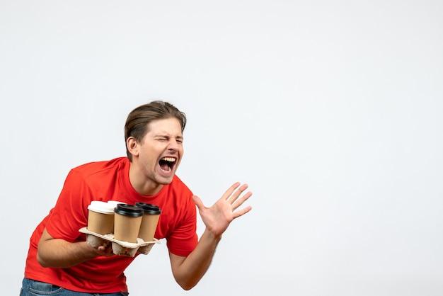 注文を保持し、白い背景で叫んで赤いブラウスで神経質な感情的な若い男の上面図
