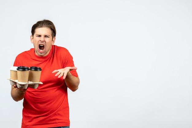 白い背景の上の注文を保持している赤いブラウスで神経質な感情的な若い男の上面図