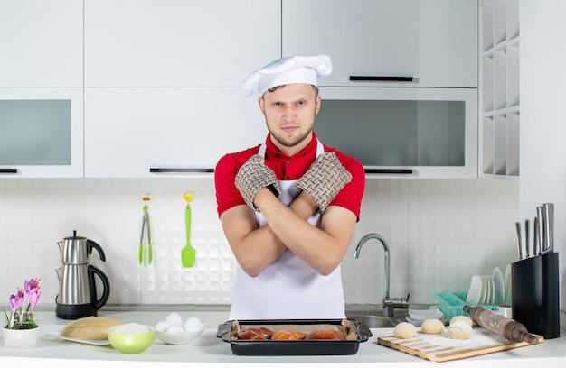 神経質な男性シェフがホルダーを着てテーブルの後ろに立ち、ペストリーの卵おろし金を載せ、白いキッチンで停止のジェスチャーをする平面図