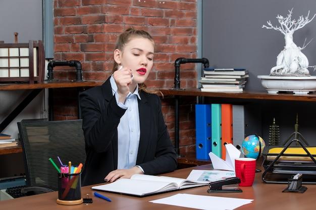 テーブルに座って、オフィスで包まれた紙を保持している神経質な女性の上面図