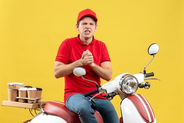 黄色の背景に注文を配信赤いブラウスと帽子を身に着けている神経質な若い男の上面図