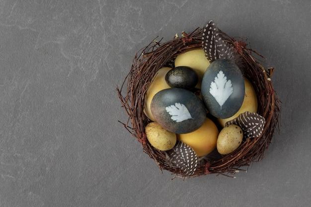 Вид сверху гнезда с естественно окрашенными пасхальными яйцами на сером фоне, копией пространства.