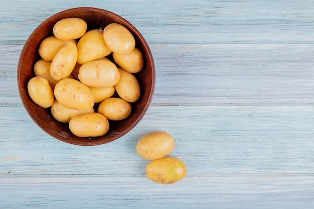 Вид сверху нового картофеля в миске на деревянной поверхности с копией пространства