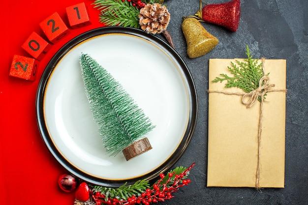 Вид сверху новогоднего фона с елкой на тарелке украшения аксессуары еловые ветки и числа на красной салфетке рядом с подарком на черном столе