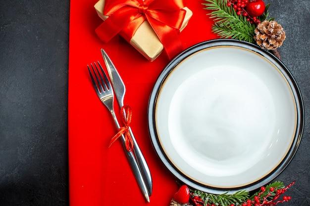 Вид сверху на новогодний фон с обеденной тарелкой, набор столовых приборов, украшения, аксессуары, еловые ветки, рядом с подарком на красной салфетке