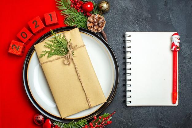 Вид сверху новогоднего фона с подарком на тарелке украшения аксессуары еловые ветки и цифры на красной салфетке и блокнот с ручкой на черном столе