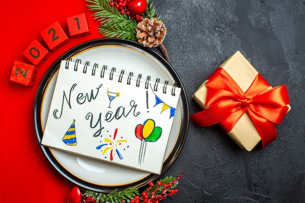 Вид сверху новогоднего фона с блокнотом с новогодними рисунками на обеденной тарелке, украшениями, еловыми ветками и числами на красной салфетке, и подарком на черном столе