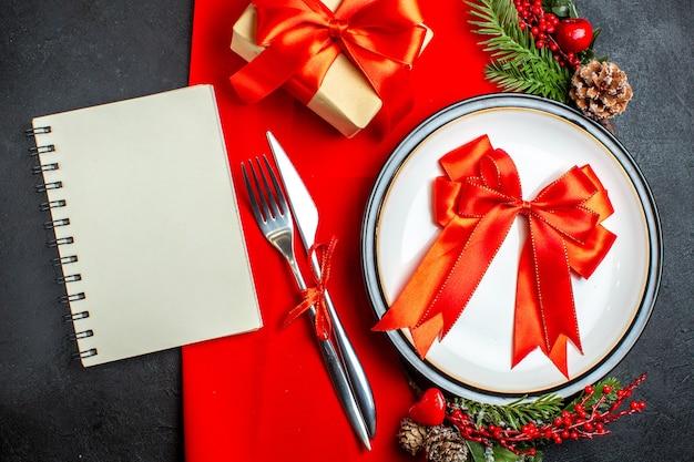 Вид сверху на новогодний фон с красной лентой на обеденной тарелке, набор столовых приборов, украшения, аксессуары, еловые ветки, рядом с подарком и спиральной записной книжкой на красной салфетке