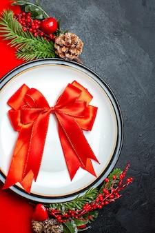 Вид сверху на новогодний фон с красной лентой на обеденной тарелке, набор столовых приборов, украшения, аксессуары, еловые ветки, рядом с подарком на красной салфетке на черном столе