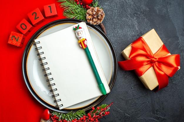 Вид сверху на новогодний фон со спиральной записной книжкой на аксессуарах для украшения обеденной тарелки еловые ветки и числа на красной салфетке и подарок с красной лентой на черном столе