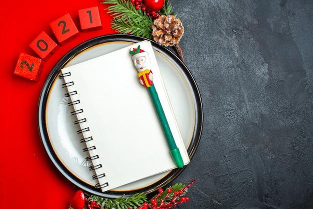 Вид сверху на новогодний фон со спиральной записной книжкой на аксессуарах для украшения обеденной тарелки еловые ветки и числа на красной салфетке на черном столе