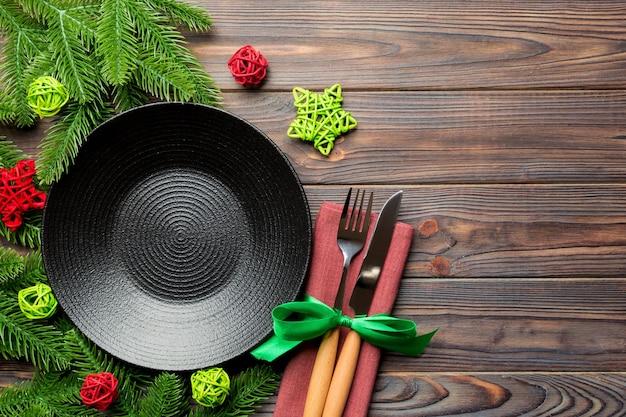 Вид сверху новогоднего ужина на праздничном деревянном фоне. композиция из тарелки, вилки, ножа, елки и украшений. с рождеством христовым концепция.