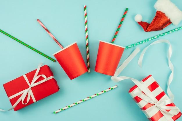 新年のパーティーアクセサリーの上面図-赤い紙コップとカクテルストロー、クリスマスツリーのつまらないもの、青い背景に包まれたギフト