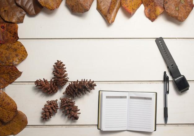 흰색 테이블 배경에 펜과 스마트 시계가 있는 메모장, 평평한 디자인