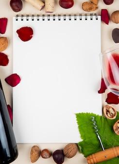 コピースペースと白い背景の上の周りの赤ワインアーモンドナッツオリーブコルク抜きと花びらのボトルとメモ帳のトップビュー