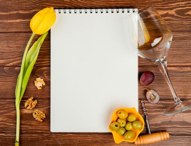 コピースペースを持つ木製の背景にオリーブホワイトワインブドウコルク抜きクルミと花とメモ帳のトップビュー