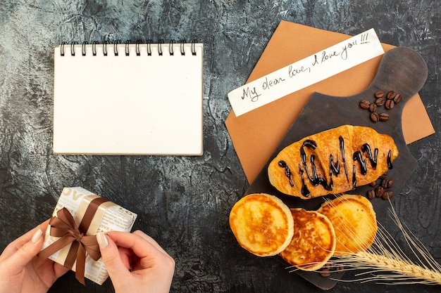 ノートとパンケーキ クロワッサンと暗いテーブルの上に手でギフト ボックスを開くおいしい朝食のトップ ビュー