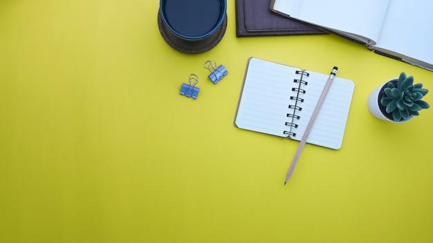 노란색 배경에 노트북, 커피 컵, 즙이 많은 식물 및 복사 공간의 상위 뷰.