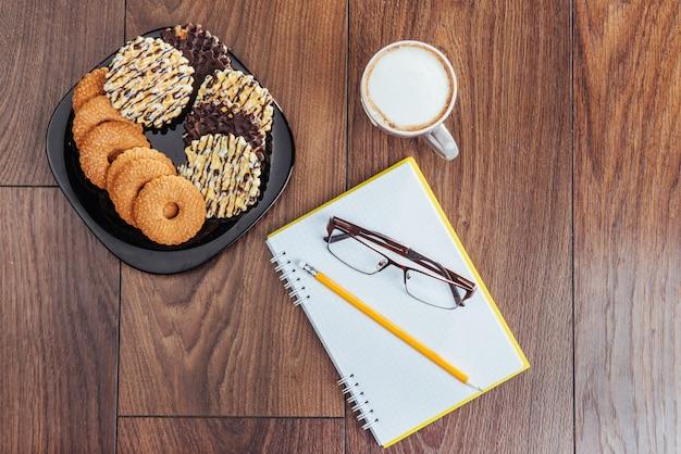 Вид сверху блокнот, канцтовары, инструменты для рисования и несколько чашек кофе.