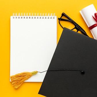 Вид сверху тетради с академической кепкой и очками