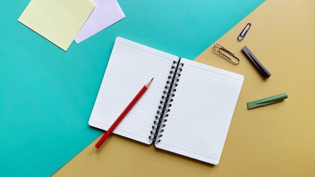 緑と黄色の背景に色鉛筆ペーパークリップと鉛筆キャップとノートブックの上面図