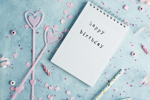 Вид сверху блокнота с пожеланием дня рождения и свечами