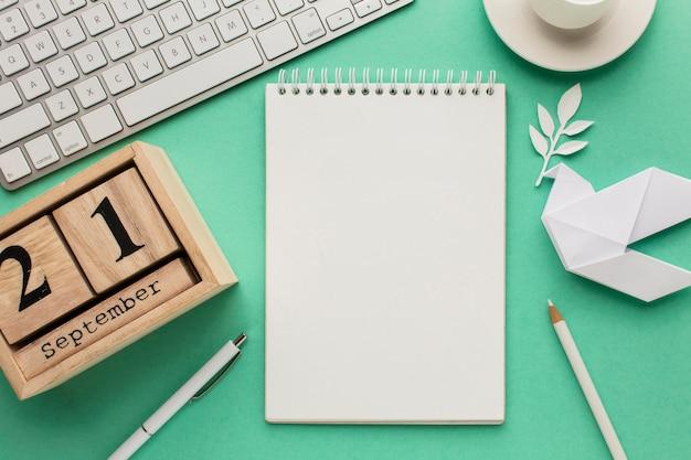 Вид сверху блокнота с клавиатурой и бумажным голубем
