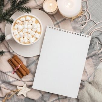 マシュマロとシナモンのマグカップとノートブックの上面図