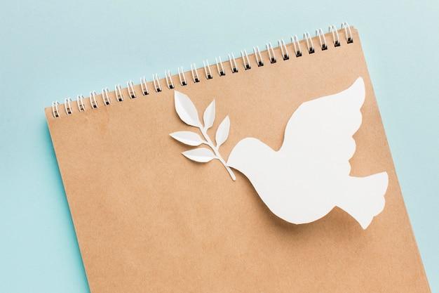 Вид сверху блокнота с бумажным голубем