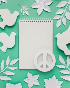 Вид сверху тетради со знаком мира и бумажных голубей