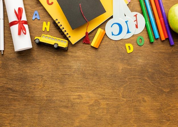 Вид сверху тетради со школьными принадлежностями и копией пространства