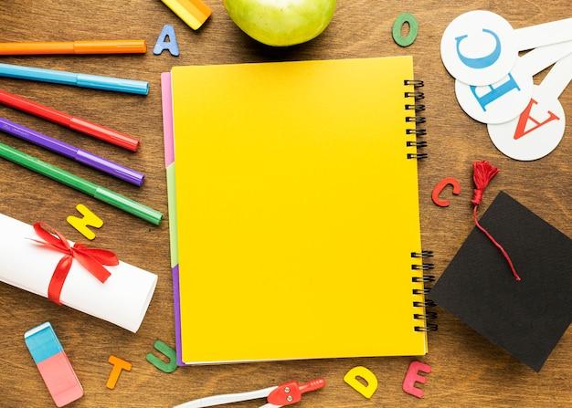 Вид сверху тетради со школьными принадлежностями и дипломом