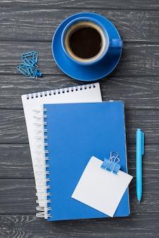 コーヒーカップとペンと木製の机の上のノートブックのトップビュー