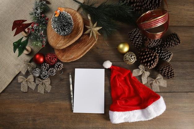 メモ帳とサンタの穴と木製のテーブルの上のクリスマスの装飾の上面図。