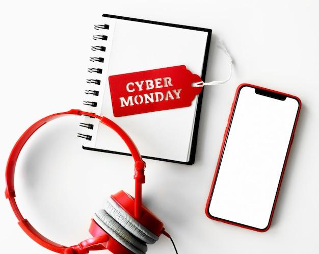 Вид сверху блокнота с наушниками и смартфоном на киберпонедельник