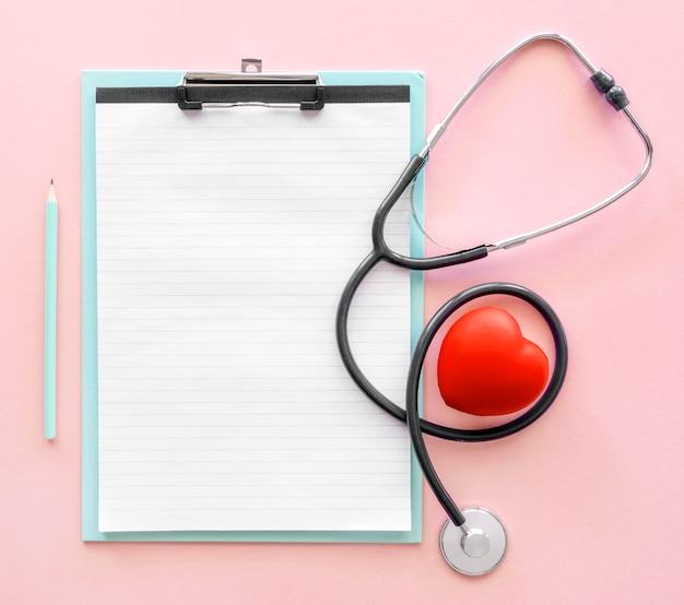 聴診器とハートの形をしたメモ帳のトップビュー