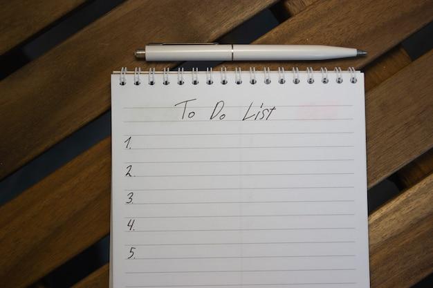 Вид сверху блокнота со списком дел, на деревянном столе, концепция целей