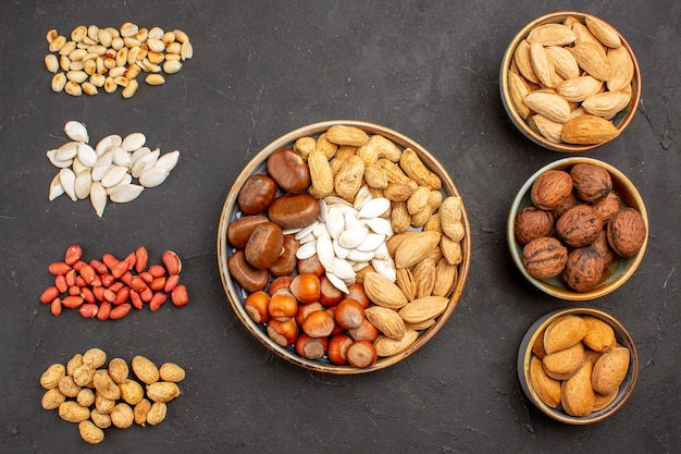 濃い灰色の表面にさまざまな新鮮なナッツを含むナッツ組成の上面図