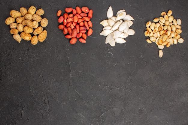 Вид сверху ореховой композиции с различными свежими орехами на темной поверхности