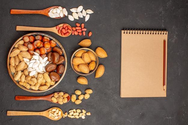 Вид сверху ореховой композиции с разными орехами на темно-серой поверхности