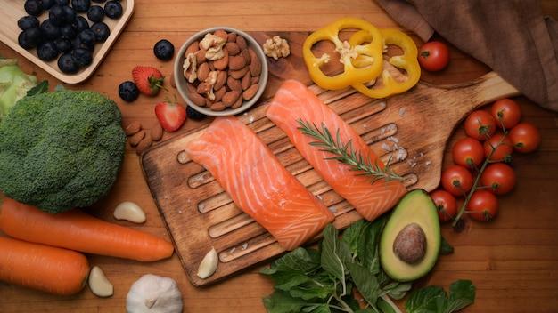 Вид сверху пищевой пищи с лососем, фруктами, овощами и семенами на деревенском столе