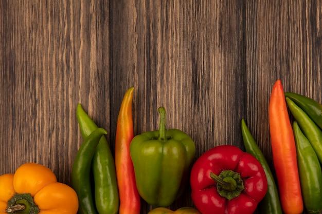 コピースペースのある木製の壁に分離された栄養ピーマンと唐辛子の上面図