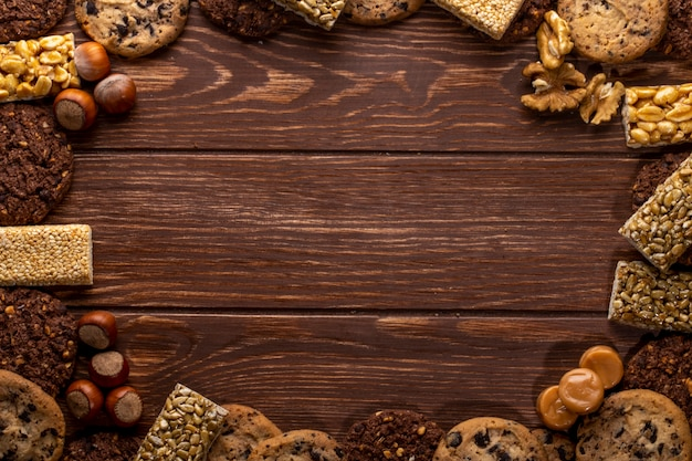 Вид сверху орехов и печенья с копией пространства на деревянном