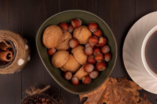 Вид сверху орехов на миске с палочками корицы с кофейными зернами на стеклянной банке на деревянной поверхности