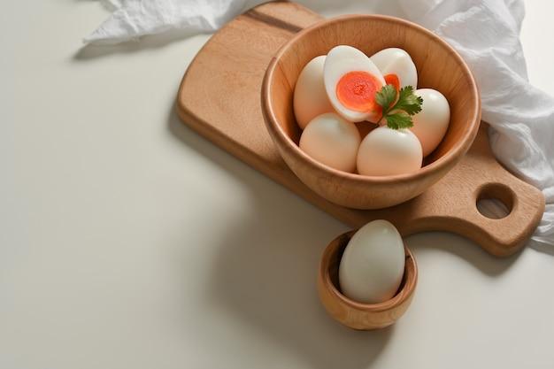 白いキッチンテーブルの上の木製のボウルにゆで卵がたくさんの上面図